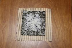 全形の焼海苔にご飯をのせて薄く広げる